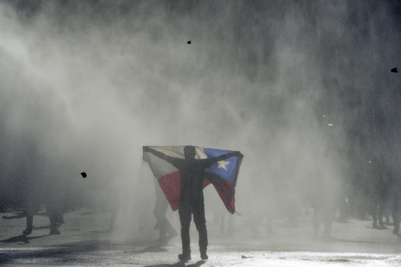 FILE - In this Oct. 25, 2019 file photo, an anti-government protester holds out a Chilean flag during clashes with police in Valparaiso, Chile. Student protests over a fare hike morphed into a nationwide call for socio-economic equality and better social services that brought millions to the streets and forced President Sebastián Piñera to increase benefits for the poor and disadvantaged and start a process of constitutional reform. (AP Photo/Matias Delacroix, File)