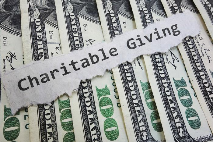Hundred dollar bills under the words Charitable Giving on a piece of paper.