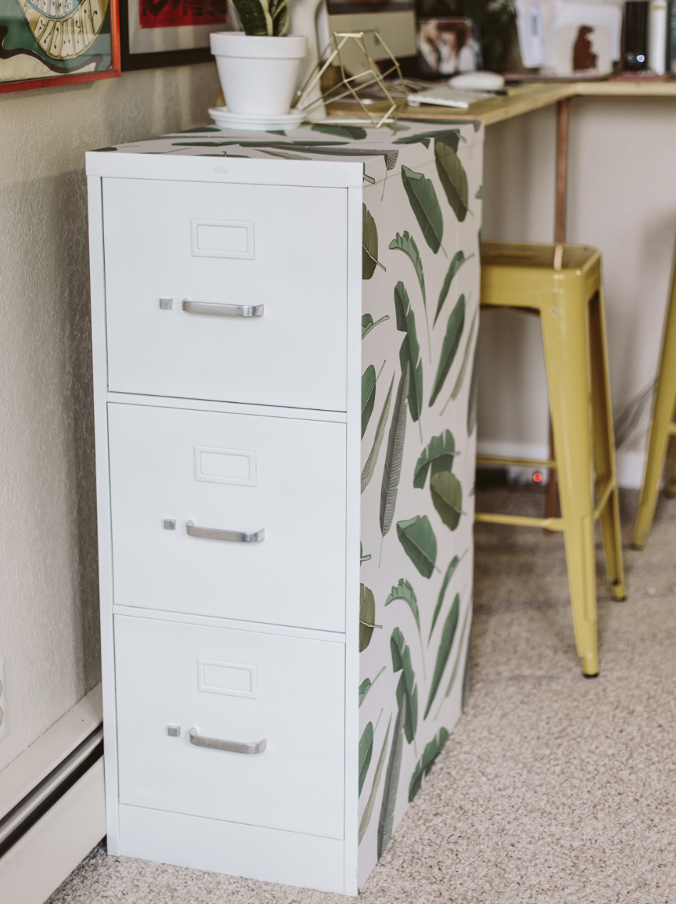"<p>Designer <a href=""https://blog.lizmorrowstudios.com/blog/2016/9/16/chic-file-cabinet-diy-restyle"" rel=""nofollow noopener"" target=""_blank"" data-ylk=""slk:Liz Morrow"" class=""link rapid-noclick-resp"">Liz Morrow</a> stuck temporary wallpaper from <a href=""https://wallsneedlove.com/products/banana-leaf-removable-wallpaper"" rel=""nofollow noopener"" target=""_blank"" data-ylk=""slk:Walls Need Love"" class=""link rapid-noclick-resp"">Walls Need Love</a> to the sides and top of an industrial white file cabinet. The banana-leaf print makes her work-from-home space feel fresh. </p>"
