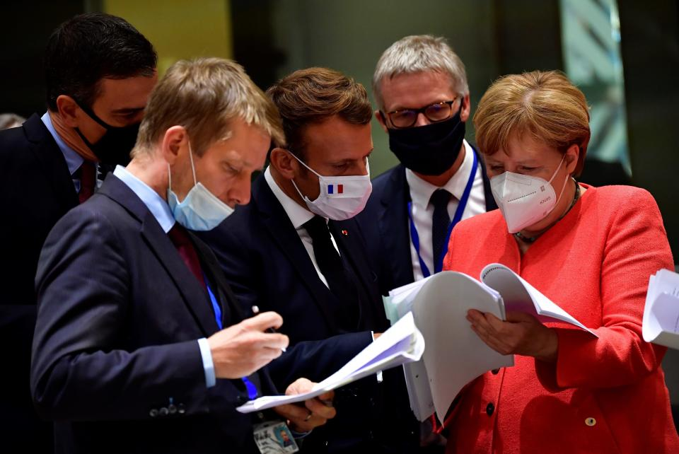 FILE - In this Monday, July 20, 2020 file photo German Chancellor Angela Merkel, right, speaks with French President Emmanuel Macron, center, during a round table meeting at an EU summit in Brussels. Britain and the European Union have struck a provisional free-trade agreement that should avert New Year's chaos for cross-border commerce and bring a measure of certainty to businesses after years of Brexit turmoil. The breakthrough on Thursday, Dec. 24, 2020 came after months of tense and often testy negotiations that whittled differences down to three key issues: fair-competition rules, mechanisms for resolving future disputes and fishing rights. (John Thys, Pool Photo via AP, File)