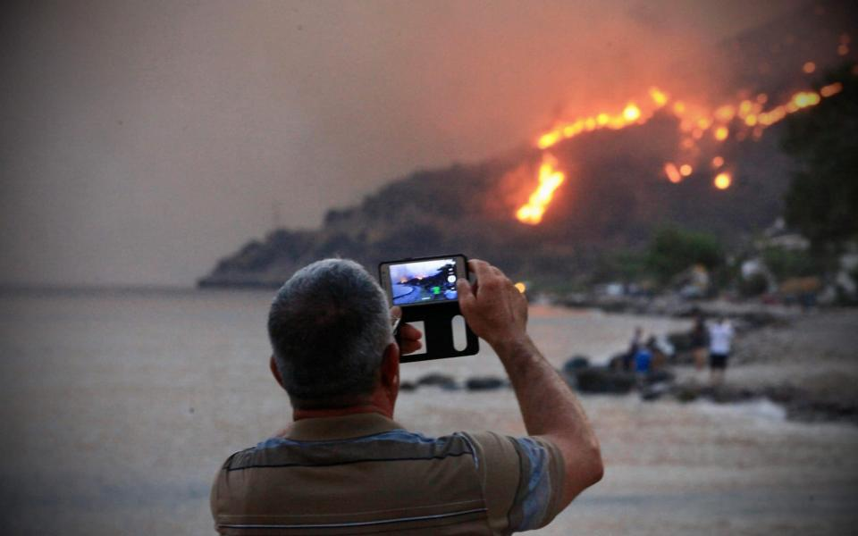 People on a beach watch the blazes spreading up a hill in the Aegean coast city of Oren, near Milas, in the holiday region of Mugla. - AFP