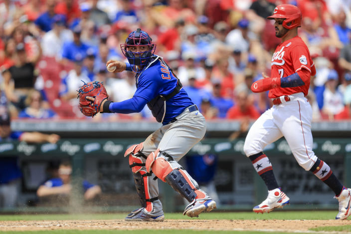 Chicago Cubs' Willson Contreras, left, looks to throw to first base as he forces out Cincinnati Reds' Eugenio Suarez at home plate during the seventh inning of a baseball game in Cincinnati, Sunday, July 4, 2021. (AP Photo/Aaron Doster)