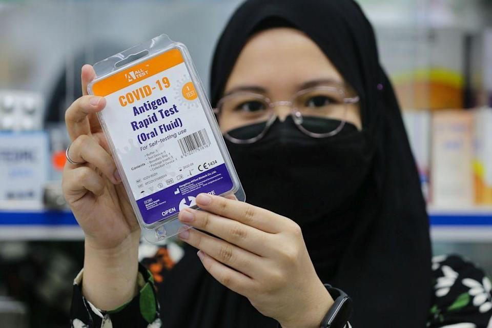 A staff holds up a Covid-19 antigen self-test kit at a pharmacy in Sri Gombak September 9, 2021. — Picture by Yusof Mat Isa