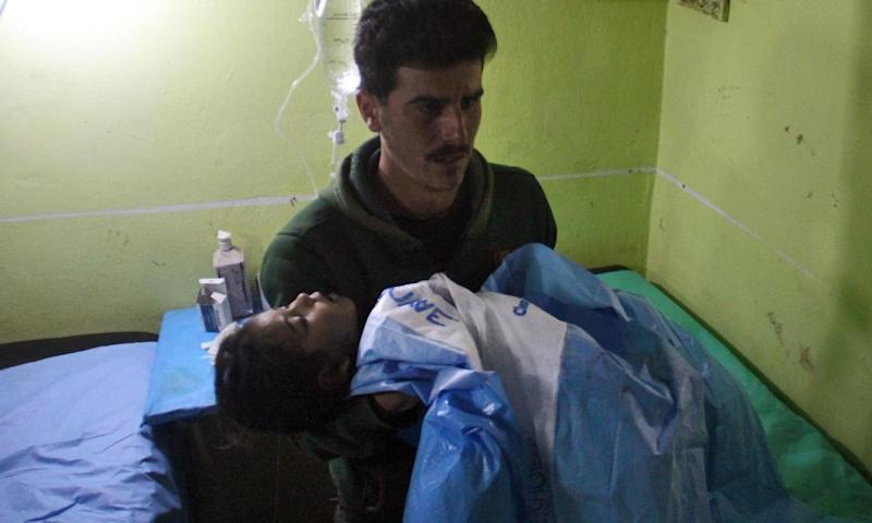 An unconscious Syrian child is carried at a hospital in Khan Sheikhun.