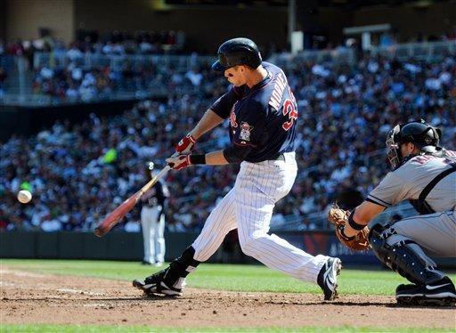 Minnesota Twins' Justin Morneau, left, hits a two-run home run against Cleveland Indians pitcher Corey Kluber as catcher Lou Marson, right, looks on in the third inning of their baseball game in Minneapolis, Sunday, Sept. 9, 2012. (AP Photo/Craig Lassig)