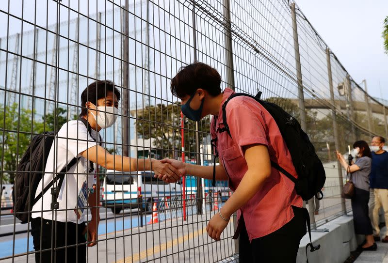 Arisa Tsubata, a nurse and a boxer, shakes hands with a staff member of the opening and closing ceremony of Tokyo 2020 Olympic Games in Tokyo