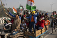 Protesting farmers riding tractors shout slogans as they march to the capital breaking police barricades during India's Republic Day celebrations in New Delhi, India, Tuesday, Jan. 26, 2021. Tens of thousands of farmers drove a convoy of tractors into the Indian capital as the nation celebrated Republic Day on Tuesday in the backdrop of agricultural protests that have grown into a rebellion and rattled the government. (AP Photo/Altaf Qadri)