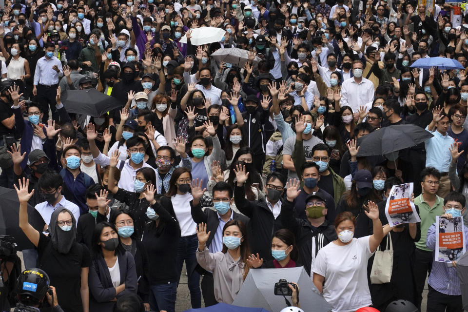 In this Tuesday, Nov. 12, 2019, photo, office workers and pro-democracy protesters hold up their hands to represent their five demands as protests continue in Central, Hong Kong. A sharp escalation of violence in Hong Kong has once again raised the question of how China's central government will respond. Experts said national security measures and deployment of the armed forces remain possibilities, though Beijing may just as likely allow destruction to continue unfolding. (AP Photo/Vincent Yu)