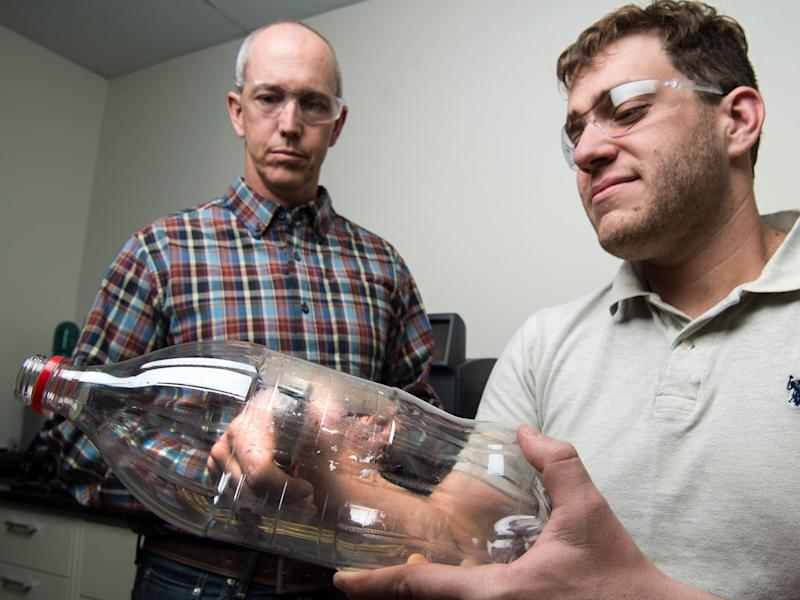 Scientists Bryon Donohoe and Nic Rorrer taking samples from a PET bottle as part of their investigation into plastic-eating enzymes: Dennis Schroeder/NREL