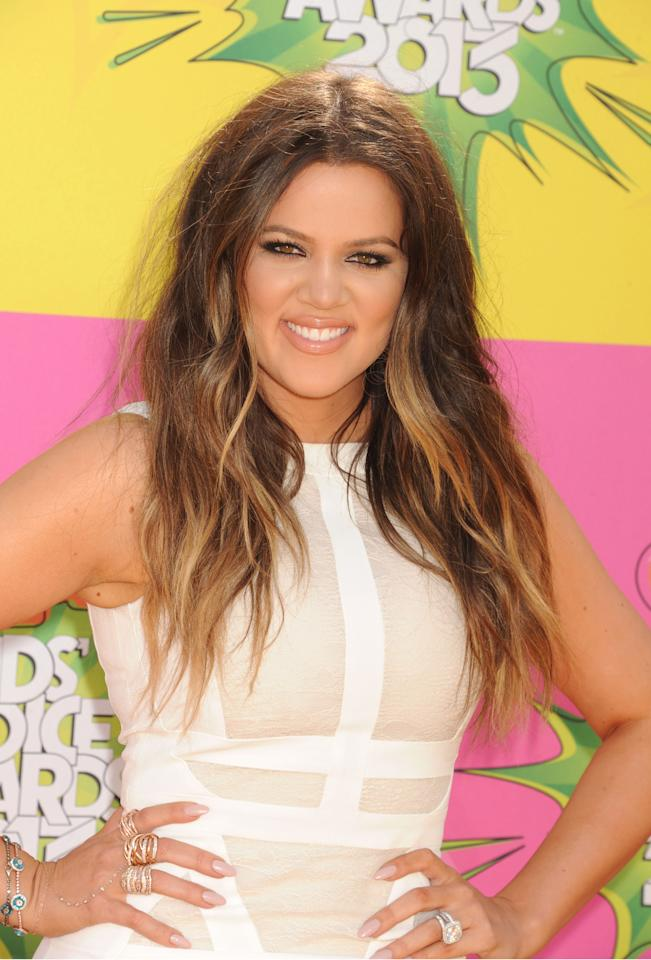 Khloe Kardashian arrives on the purple carpet in a white bondage dress. Her ombre hair stands out. She keeps her makeup simple with nude lips and heavily lined eyes.