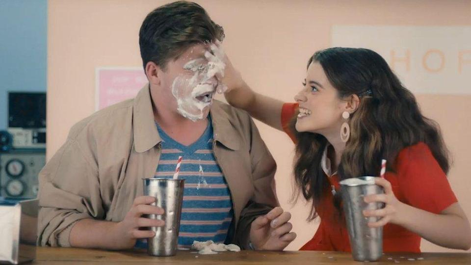 Screenshot from the video of a woman smearing milkshake on a man's face