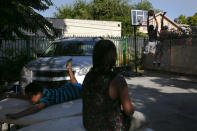 Aiden Figueroa, foreground, watches as James Posey III, far right, and Aiden's brother, Darius play basketball in the backyard of their home in the Watts neighborhood of Los Angeles, Monday, June 15, 2020. (AP Photo/Jae C. Hong)