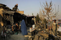 An Afghan man prepares to throw a used tire from the roof of his shop as a burqa clad woman walks past at a market place in Kabul, Afghanistan, Wednesday, Dec. 4, 2019. (AP Photo/Altaf Qadri)