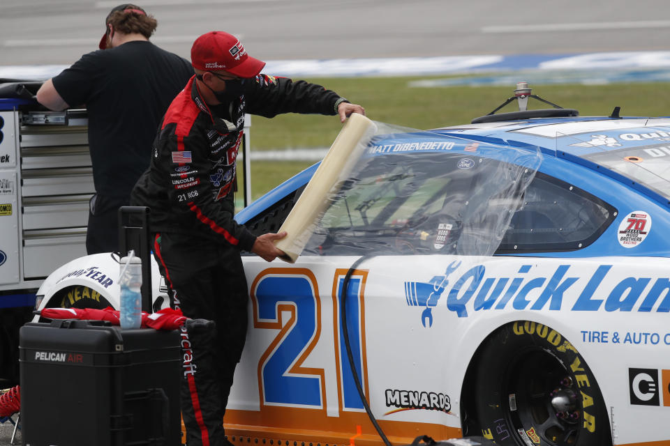 Crews cover the car of driver Matt DiBenedetto as inclement weather rolls in prior to a NASCAR Cup Series auto race at Talladega Superspeedway in Talladega Ala., Sunday, June 21, 2020. (AP Photo/John Bazemore)