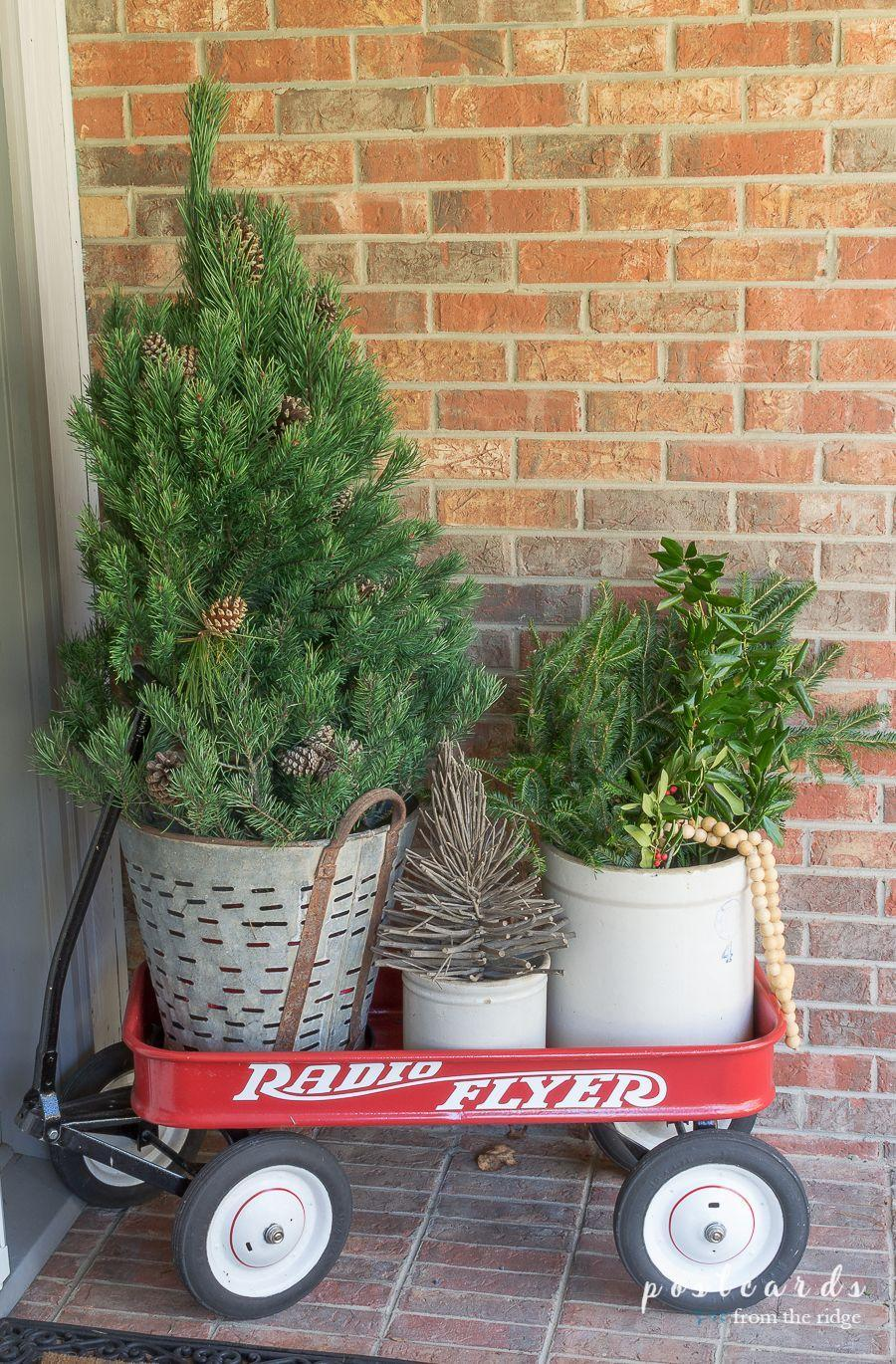 """<p>An iconic red wagon transforms into a perfect piece of holiday porch decor: Use it as a planter, a basket for accessories — whatever you can dream up.<br></p><p><strong><em>Get the tutorial at <a href=""""https://www.postcardsfromtheridge.com/2017/11/cozy-christmas-front-porch.html"""" rel=""""nofollow noopener"""" target=""""_blank"""" data-ylk=""""slk:Postcards from the Ridge"""" class=""""link rapid-noclick-resp"""">Postcards from the Ridge</a>.</em></strong></p>"""