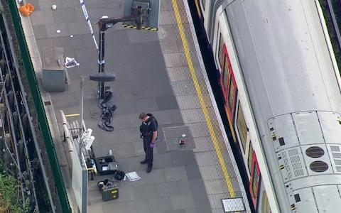 a police officer works at the Parsons Green Underground Station after an explosion  - Credit: AP