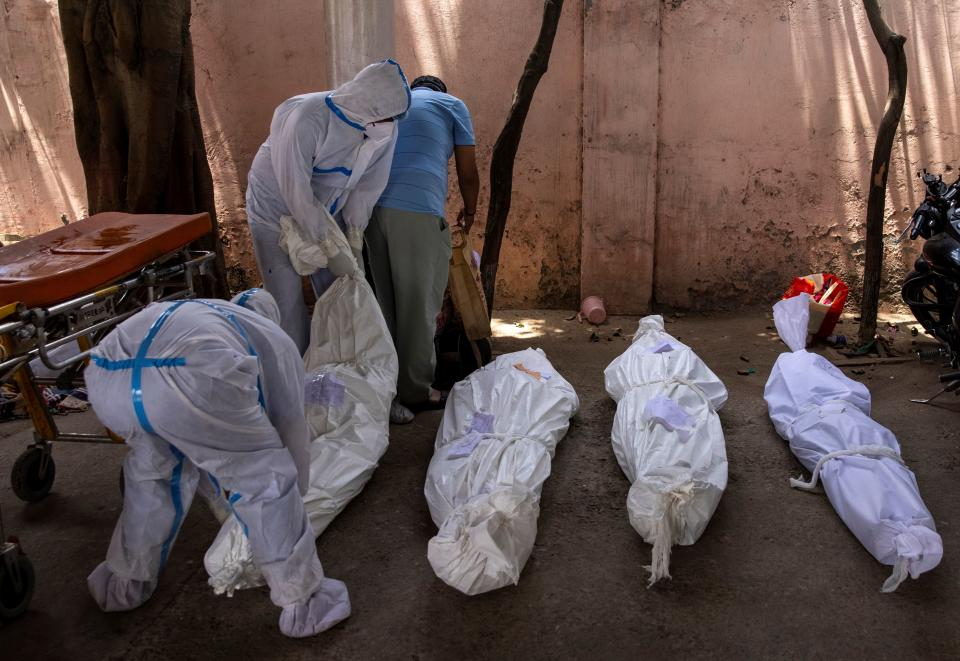 Healthcare workers place the body of a person, who died due to the coronavirus disease, on the ground for cremation at a crematorium ground in New Delhi, India.