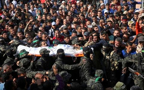 Mourners carry the body of Hamas militant commander Nour el-Deen Barakas, who was killed during the Israeli raid - Credit: Adel Hana/AP