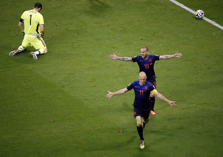Robben and Sneijder of the Netherlands celebrate after scoring against Spain's goalkeeper Casillas during their 2014 World Cup Group B soccer match at the Fonte Nova arena in Salvador