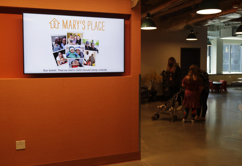 A video display shows photos and the logo for Mary's Place, a family homeless shelter located inside an Amazon corporate building on the tech giant's Seattle campus, Wednesday, June 17, 2020. The shelter marks a major civic contribution bestowed by Amazon to the hometown it has rapidly transformed. (AP Photo/Ted S. Warren)