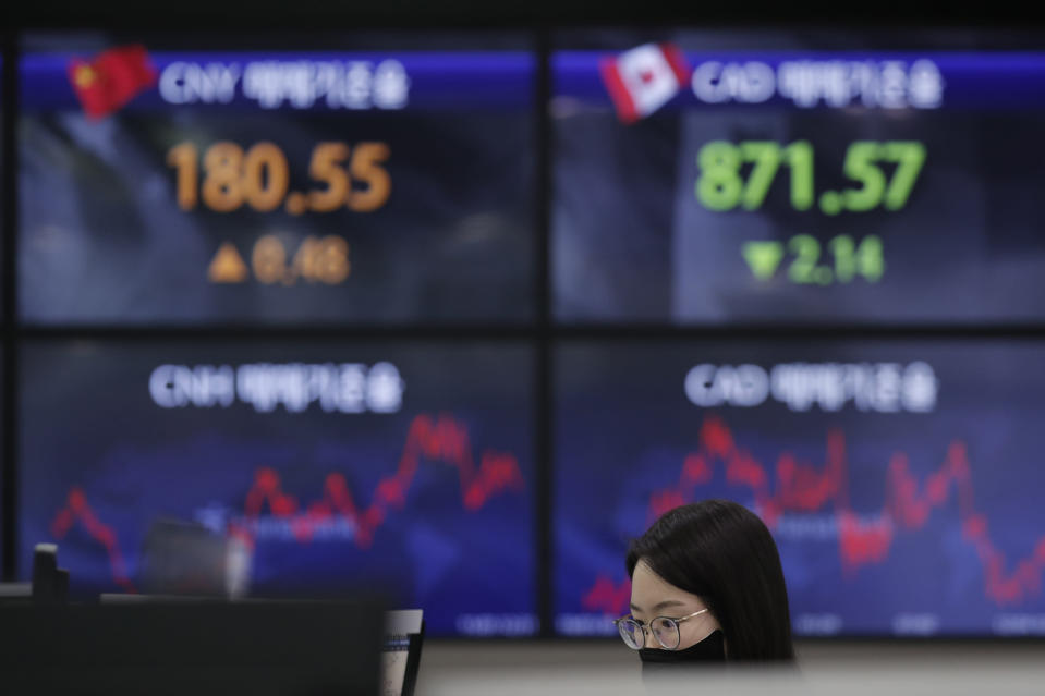 An employee of a bank watches computer monitors near screens showing the foreign exchange rates at the foreign exchange dealing room in Seoul, South Korea, Thursday, Feb. 4, 2021. Asian shares mostly fell Thursday as caution set in over company earnings reports, recent choppy trading in technology stocks and prospects for more economic stimulus for a world battling a pandemic. (AP Photo/Lee Jin-man)
