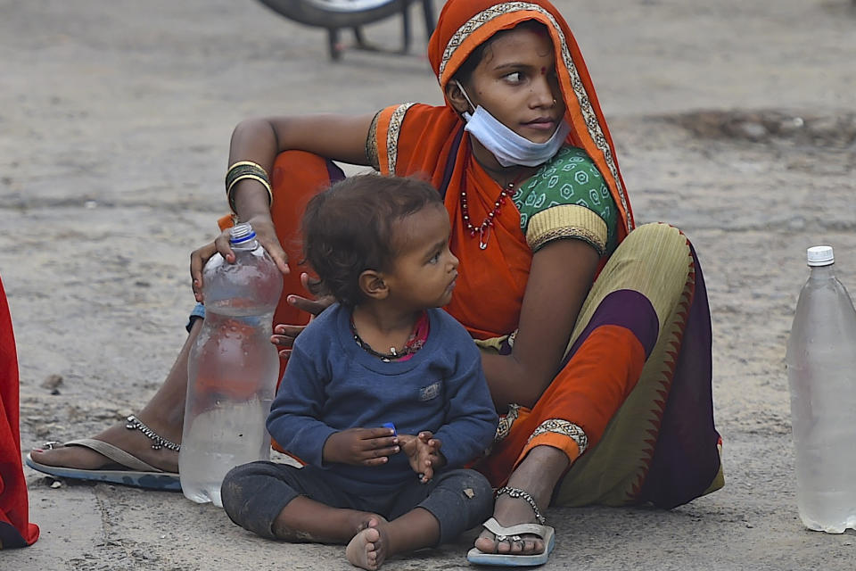 A migrant worker with her child sits on a roadside as she takes a break on her journey towards their respective hometown state during a government-imposed nationwide lockdown as a preventive measure against the COVID-19 coronavirus, in Faridabad on May 13, 2020. (Photo by Money SHARMA / AFP) (Photo by MONEY SHARMA/AFP via Getty Images)