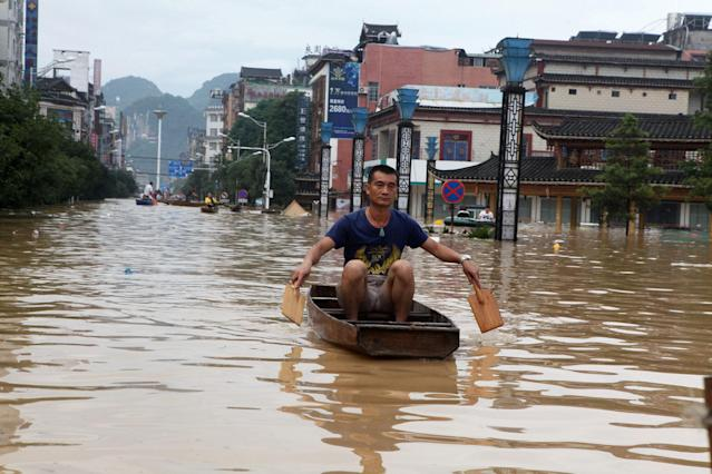 <p>A man makes his way with a wooden boat through a flooded area in Liuzhou, Guangxi province, China ,July 2, 2017. (Photo: Stringer/Reuters) </p>