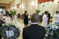 With six feet in between them, mourners pay their respects during the viewing of Joanne Paylor, 62, of Washington, inside the chapel at Cedar Hill Cemetery, in Suitland-Silver Hill, Md., Sunday, May 3, 2020. The original funeral for Paylor, who the family believes died of a heart attack, was delayed for close to two months while her family hoped social distancing guidelines would be lifted. Despite not having died from coronavirus, almost every aspect of her funeral has been impacted by the pandemic. (AP Photo/Jacquelyn Martin)