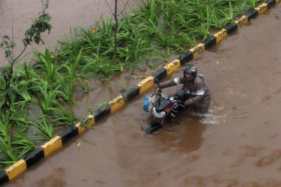 A man pushes a motorcycle through a flooded road during heavy rains in Mumbai, India on August 04, 2020. (Photo by Himanshu Bhatt/NurPhoto via Getty Images)