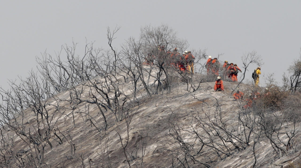A hand crew looks on from a burnt hillside as firefighters fight a wildfire in the Angeles National Forest north of Glendora, Calif., Monday, Sept. 3, 2012. A day after the wildfire broke out near a campground and forced the evacuation of thousands of campers and picnickers it had grown to more than 4,100 acres, or roughly 6 square miles, and was just five percent contained. (AP Photo/Jason Redmond)