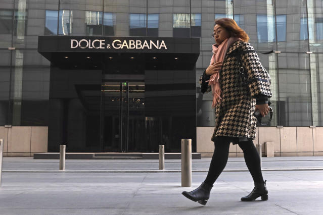 In this Nov. 25, 2018, photo, a woman walks past a Dolce&Gabbana retail outlet in Beijing, China. Don't mess with China - and its 770 million internet users. That's the lesson Dolce&Gabbana learned the hard way after Chinese netizens expressed their outrage at a promotional video the company made for the Chinese market and insulting comments made on Instagram, though the company blamed hackers for the latter. As retailers pulled their merchandise from shelves, co-founders Domenico Dolce and Stefano Gabbana went on camera to apologize to the Chinese people. (AP Photo/Ng Han Guan)