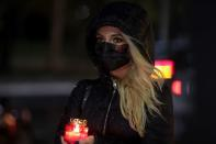A woman holding a lit candle attends an event that commemorates the 65 victims of the Colectiv fire
