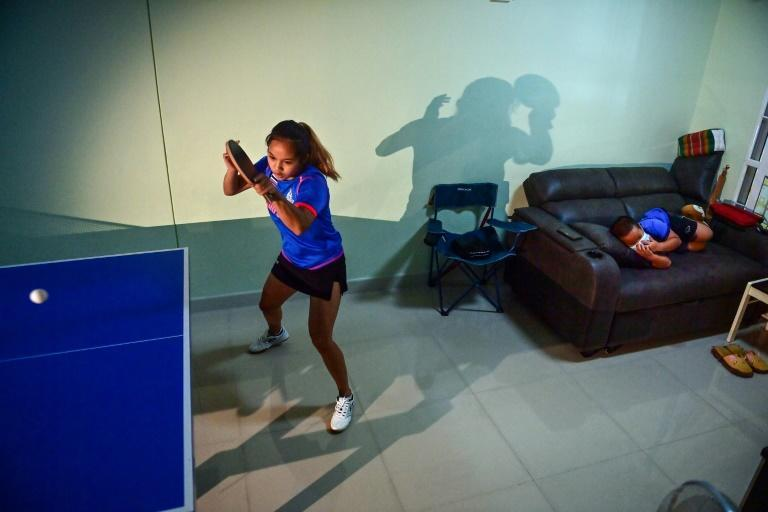 """Thailand table tennis player Orawan Paranang trains for the Tokyo Olympics in her makeshift living room practice facility as her nephew Theerawat """"Leo"""" watches television on the sofa at their home in Nonthaburi, near Bangkok"""