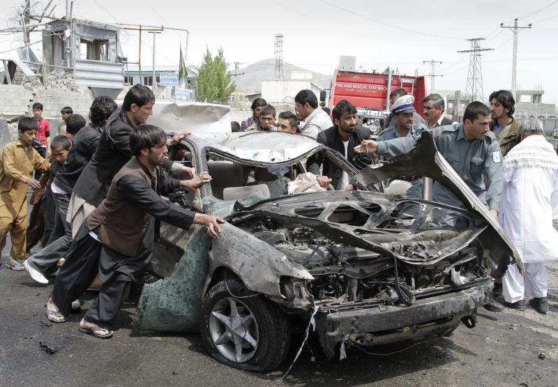 Afghans push a damaged car away from the scene of a militant attack in Kabul, Afghanistan, Wednesday, May 2, 2012.  A suicide car bomber and Taliban militants disguised in burqas attacked a compound housing hundreds of foreigners in the Afghan capital on Wednesday, officials and witnesses said.  The Taliban said the attack was a response to President Barack Obama's surprise visit just hours earlier. (AP Photo/Ahmad Jamshid)