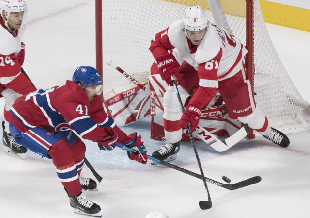 Detroit Red Wings' Jacob De La Rose (61) battles for the puck against Montreal Canadiens' Paul Byron (41) during second-period NHL hockey game action in Montreal, Thursday, Oct. 10, 2019. (Graham Hughes/The Canadian Press via AP)