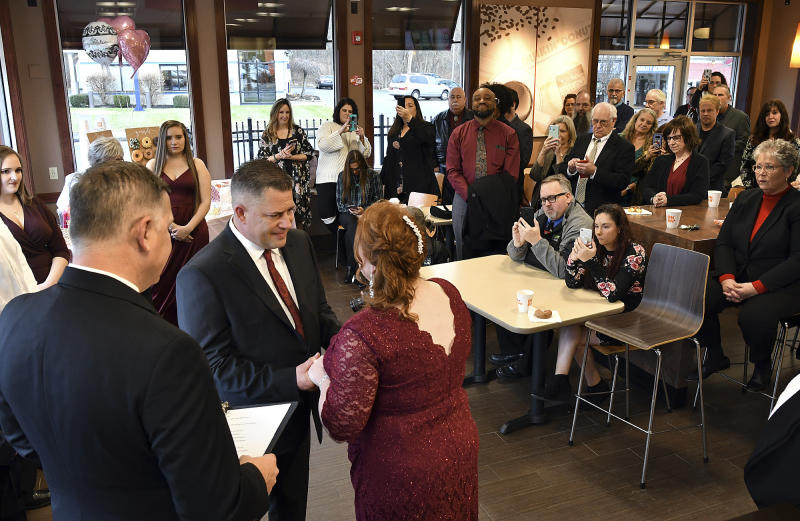 Jason Roy and Valerie Sneade say their vows in front of friends and family at the Dunkin' Donuts on Friday, Dec. 27, 2019 in Worcester, Mass.  The couple reunited for their wedding vows at the Dunkin' Donuts where their young love splintered nearly thirty years ago. Except for a couple of chance encounters, Sneade and Roy mostly didn't see each other for 25 years after a conversation about their future at the same donut shop in 1992 led the young couple to slowly cut ties. Sneade and Roy blame misunderstandings at the time and words that didn't come out right.  (Rick Cinclair/Worcester Telegram & Gazette via AP)