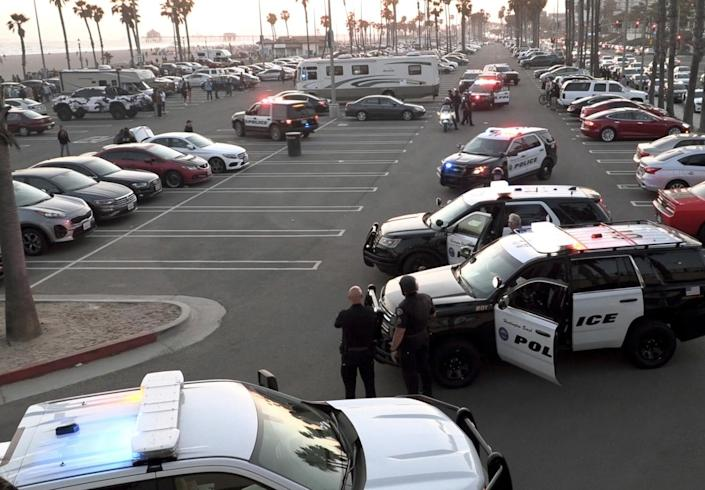 Huntington Beach police stage in the parking lot near Lifeguard Tower 13.