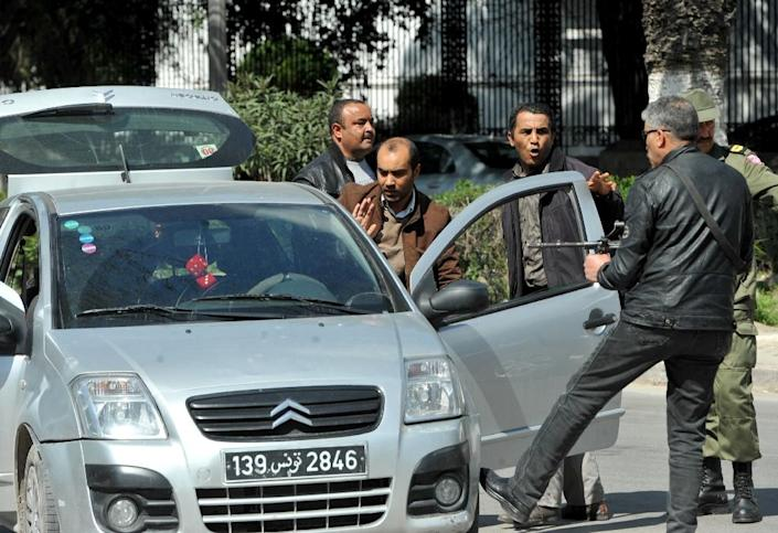 Armed Tunisian police in plain clothes stop a vehicle as security forces secure the area after gunmen attacked Tunis' Bardo Museum (AFP Photo/Fethi Belaid)