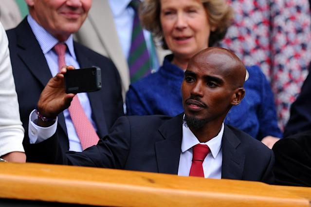 LONDON, ENGLAND - JUNE 26: Mo Farah uses his mobile phone before the Ladies' Singles second round match between Eugenie Bouchard of Canada and Ana Ivanovic of Serbia on day three of the Wimbledon Lawn Tennis Championships at the All England Lawn Tennis and Croquet Club on June 26, 2013 in London, England. (Photo by Mike Hewitt/Getty Images)