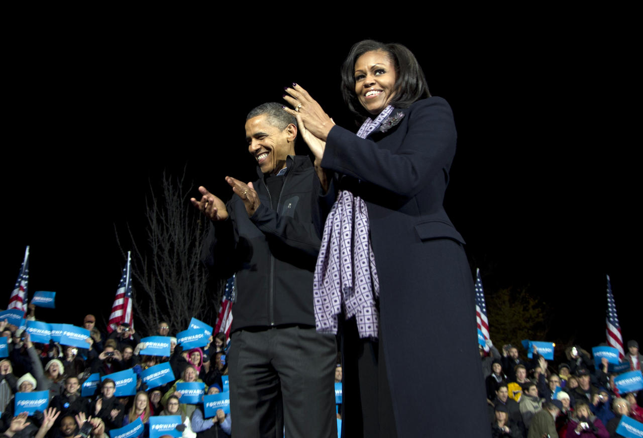President Barack Obama and first lady Michelle Obama acknowledge the crowd at his final campaign stop on the evening before the 2012 election, Monday, Nov. 5, 2012, in the downtown Des Moines, Iowa. (AP Photo/Carolyn Kaster)