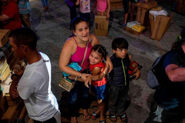 PHOTO: A girl cries next to her mother after police evacuated people breaking into a warehouse filled with supplies in Ponce, Puerto Rico on Jan. 18, 2020. (Ricardo Arduengo/AFP via Getty Images)
