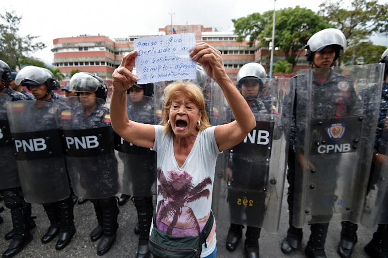 A woman demonstrating against Maduro holds a sign urging the military to uphold the constitution