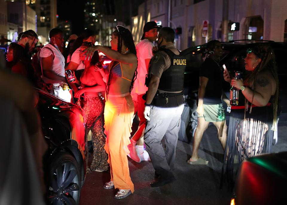 MIAMI BEACH, FLORIDA - MARCH 21: A Miami Dade police officer directs people out of the area as an 8pm curfew goes into effect on March 21, 2021 in Miami Beach, Florida. College students have arrived in the South Florida area for the annual spring break ritual, prompting city officials to impose an 8pm to 6am curfew as the coronavirus pandemic continues. Miami Beach police have reported hundreds of arrests and stepped up deployment to control the growing spring break crowds. (Photo by Joe Raedle/Getty Images)
