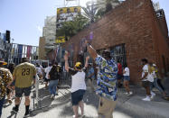 Baseball fans celebrate as the gates open up before a baseball game between the Arizona Diamondbacks and the San Diego Padres Thursday, April 1, 2021, on opening day in San Diego. (AP Photo/Denis Poroy)