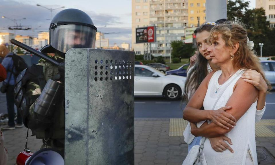 Two women talk with a riot police officer as police block a part of a street in the capital Minsk.