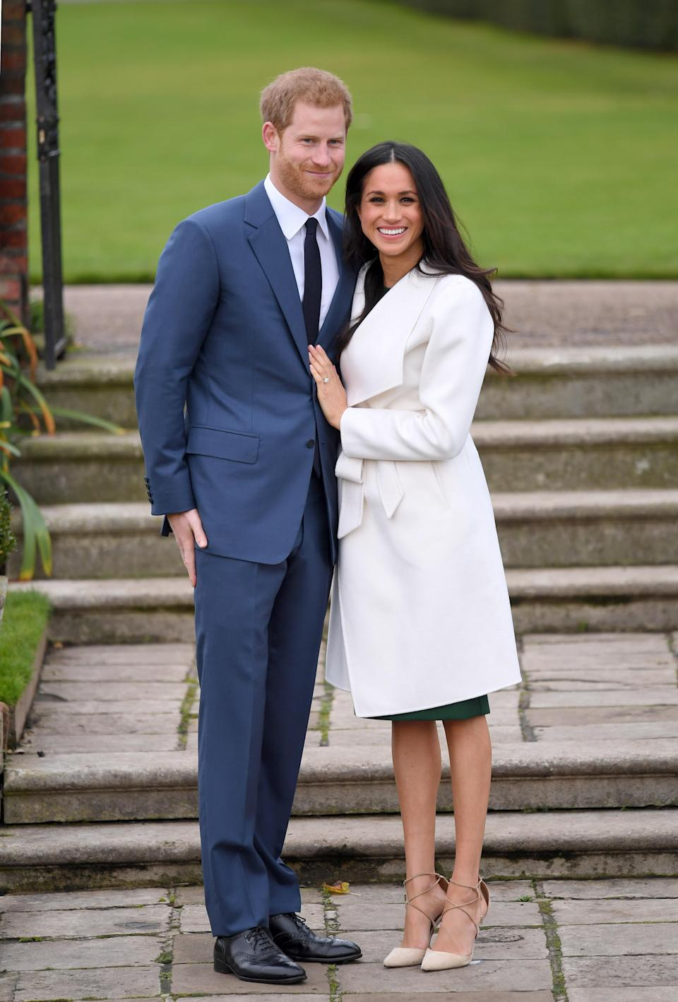 <p>For her official engagement appearance, Meghan chose a white belted wrap coat by Canadian label Line along with a black dress and suede nude heels.<br><i>[Photo: Getty]</i> </p>