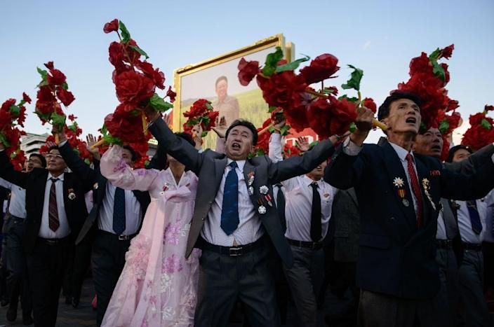 Participants wave flowers at North Korean leader Kim Jong-Un as they pass through Kim Il-Sung square during a mass military parade in Pyongyang in October 2015 (AFP Photo/Ed Jones)