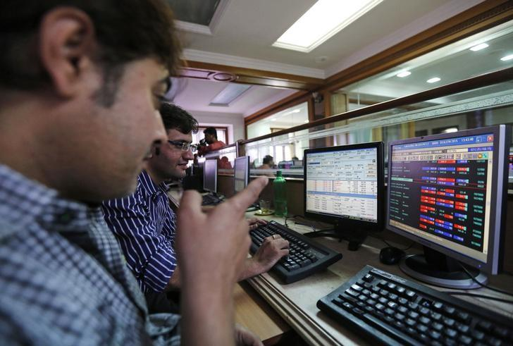 Brokers trade on computer terminals at a stock brokerage firm in Mumbai