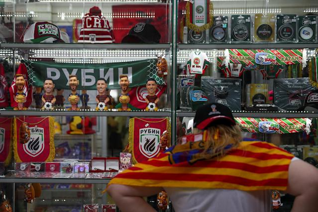 A woman, wearing a Spanish soccer club Barcelona's flag, stands next to figures depicting Argentina's star Lionel Messi and Portugal's star Cristiano Ronaldo inside a souvenirs shop in Kazan, Russia, June 20, 2018. As well as shooting all the matches, Reuters photographers are producing pictures showing their own quirky view from the sidelines of the World Cup. REUTERS/Sergio Perez