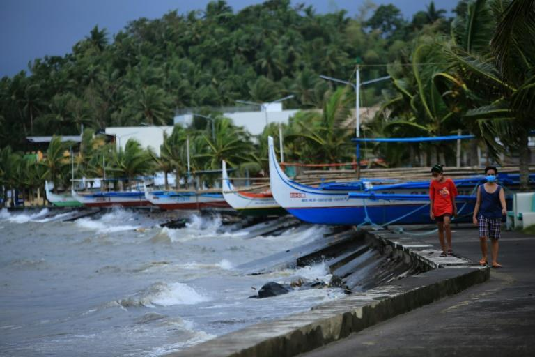 Residents walk past parked wooden boats along a boulevard in Legazpi
